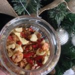 Picture of a jar of granola next to a Christmas tree.